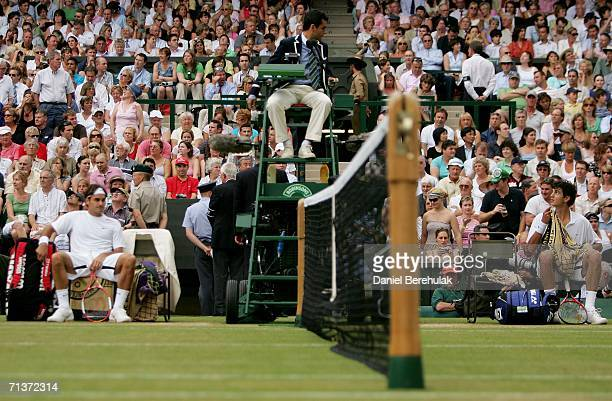 Mario Ancic of Croatia talks to umpire Carlos Ramos sits between games against Roger Federer of Switzerland during day nine of the Wimbledon Lawn...