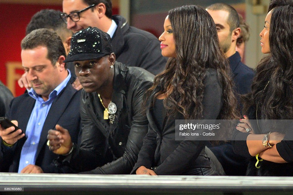 Mario Balotelli and Fanny look on before the Serie A match between AC Milan and Udinese Calcio at Giuseppe Meazza Stadium on October 19, 2013 in Milan, Italy