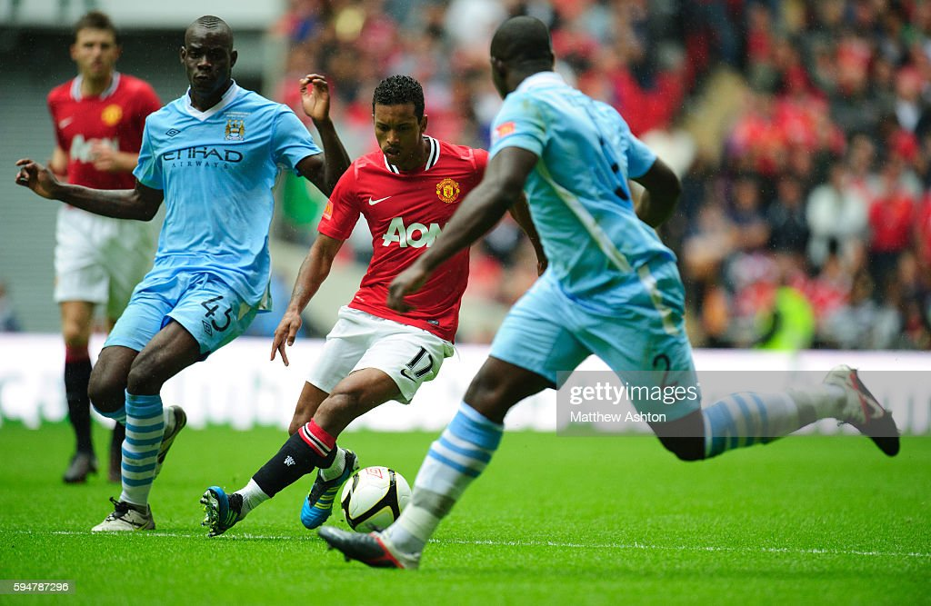 Mario Balotelli and Micah Richards of Manchester City try and stop Nani of Manchester United