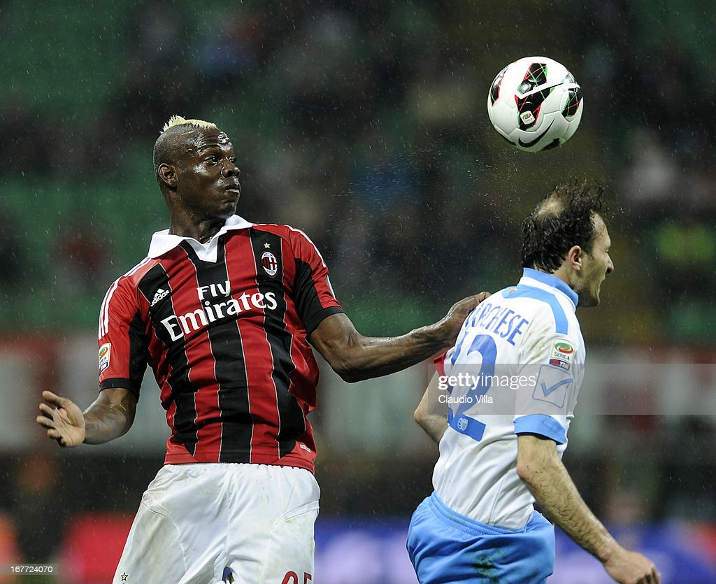 Mario Balotelli of AC Milan and Giovanni Marchese of Calcio Catania (R) compete for the ball during the Serie A match between AC Milan and Calcio Catania at San Siro Stadium on April 28, 2013 in Milan, Italy.