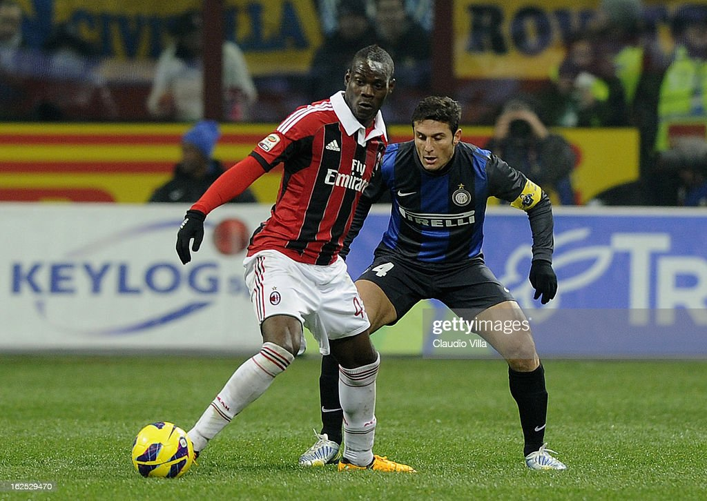 Mario Balotelli of AC Milan (L) and Javier Zanetti of FC Inter Milan compete for the ball during the Serie A match FC Internazionale Milano and AC Milan at San Siro Stadium on February 24, 2013 in Milan, Italy.