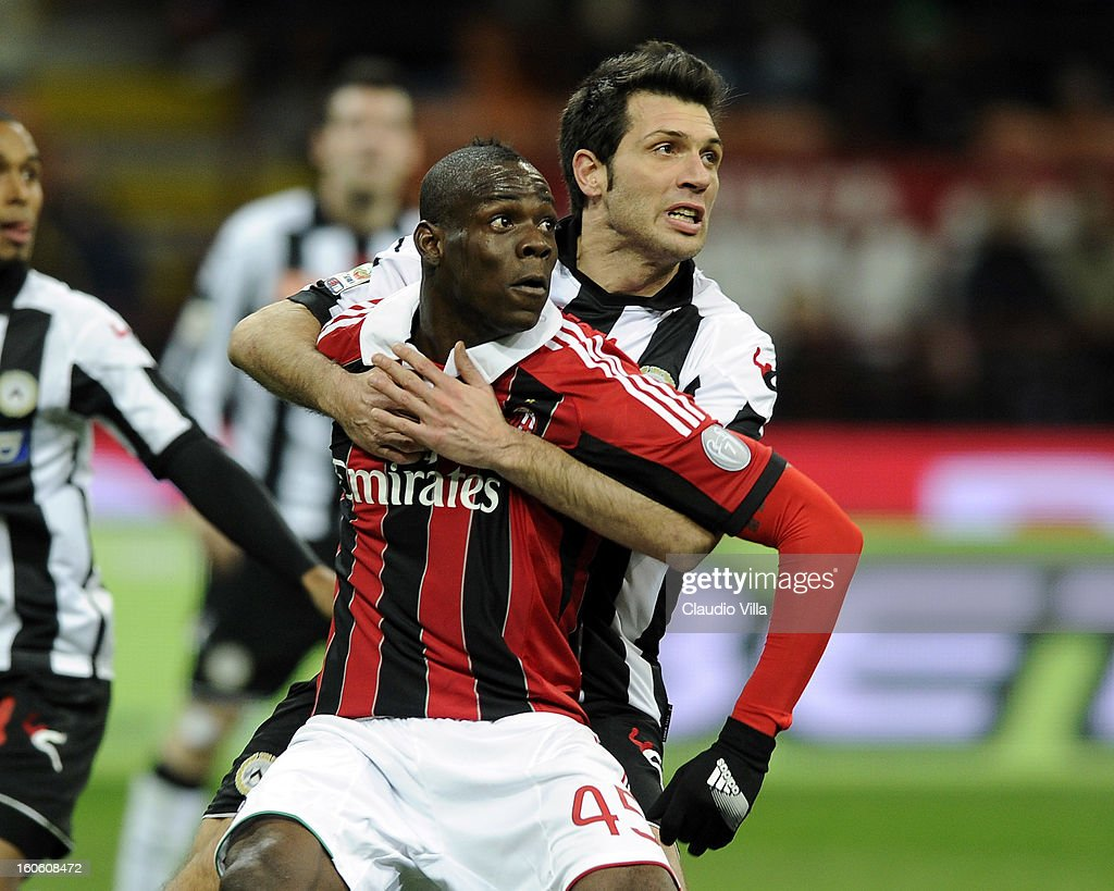 Mario Balotelli of AC Milan is held by Maurizio Domizzi of Udinese Calcio (R) during the Serie A match between AC Milan and Udinese Calcio at San Siro Stadium on February 3, 2013 in Milan, Italy.