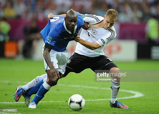 Mario Balotelli of Italy battles for the ball with Holger Badstuber of Germany during the UEFA EURO 2012 semi final match between Germany and Italy...