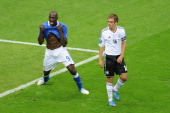 Mario Balotelli of Italy celebrates scoring the opening goal as Philipp Lahm of Germany shows his dejection during the UEFA EURO 2012 semi final...