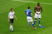 Mario Balotelli of Italy celebrates with teammate Claudio Marchisio after scoring his team's second goal as Philipp Lahm of Germany shows his...