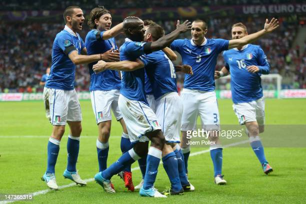 Mario Balotelli of Italy celebrates with teammates after scoring the opening goal during the UEFA EURO 2012 semi final match between Germany and...