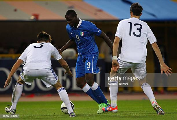 Mario Balotelli of Italy competes for the ball with Gianluca Bollini and Fabio Vitaioli of San Marino during the international friendly match between...