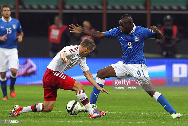 Mario Balotelli of Italy competes for the ball with Nicolai Stokholm of Denmark during the FIFA 2014 World Cup qualifier match between Italy and...