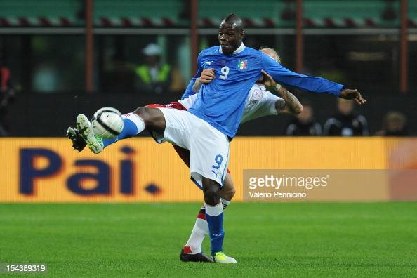 Mario Balotelli of Italy is challenged by Simon Kjaer of Denmark during the FIFA 2014 World Cup qualifier match between Italy and Denmark at Stadio...