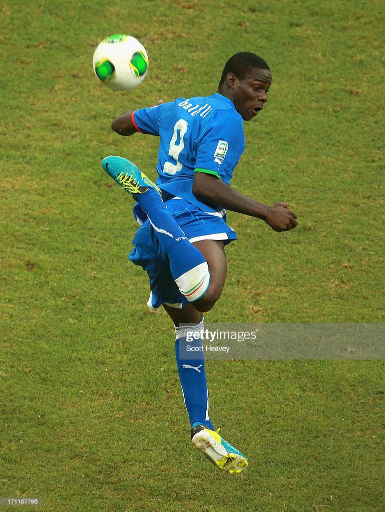 Mario Balotelli of Italy jumps for the ball during the FIFA Confederations Cup Brazil 2013 Group A match between Italy and Brazil at Estadio Octavio Mangabeira (Arena Fonte Nova Salvador) on June 22, 2013 in Salvador, Brazil.