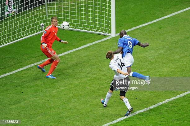 Mario Balotelli of Italy jumps next to Holger Badstuber of Germany to score the opening goal past Manuel Neuer of Germany during the UEFA EURO 2012...