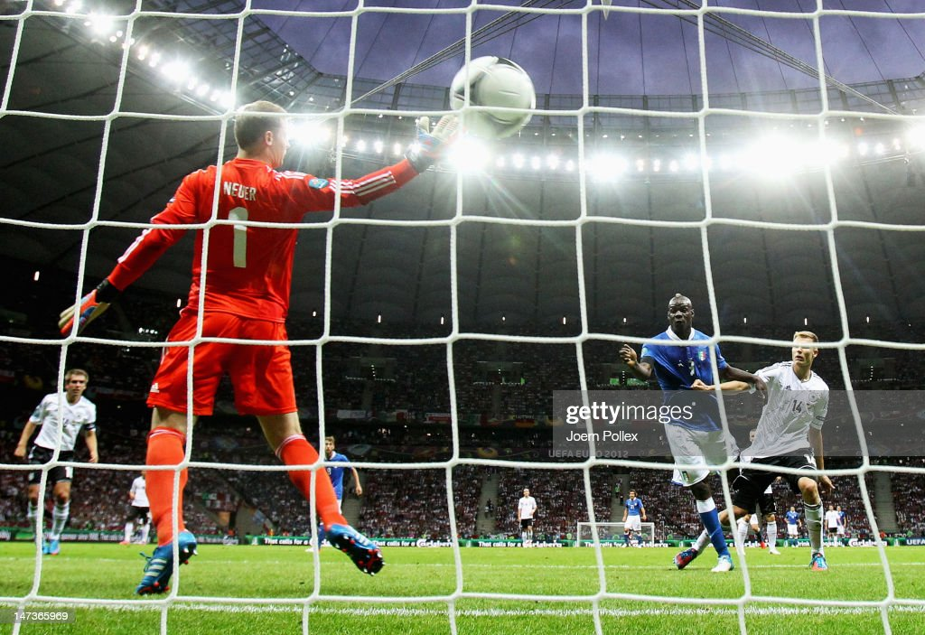 Mario Balotelli (R) of Italy jumps next to Holger Badstuber of Germany to score the opening goal past Manuel Neuer of Germany during the UEFA EURO 2012 semi final match between Germany and Italy at National Stadium on June 28, 2012 in Warsaw, Poland.