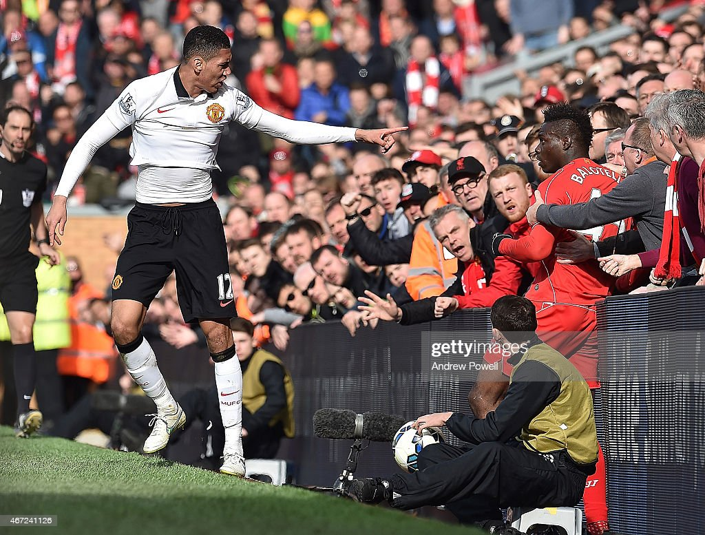 Mario Balotelli of Liverpool and Chris Smalling of Manchester United end up in with the fans during the Barclays Premier League match between Liverpool and Manchester United at Anfield on March 22, 2015 in Liverpool, England.