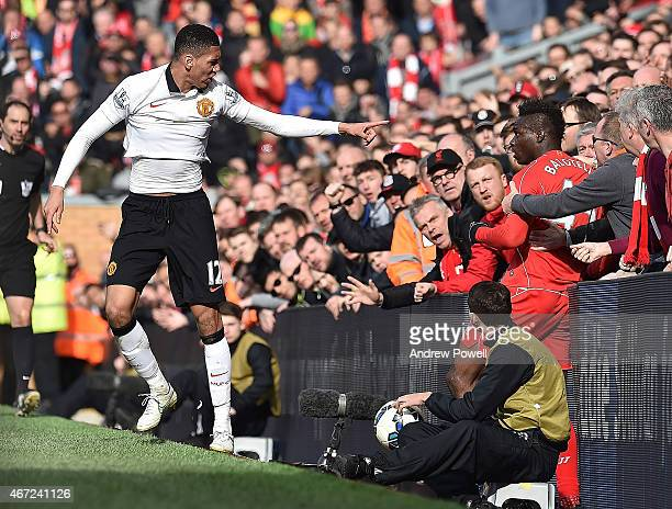 Mario Balotelli of Liverpool and Chris Smalling of Manchester United end up in with the fans during the Barclays Premier League match between...