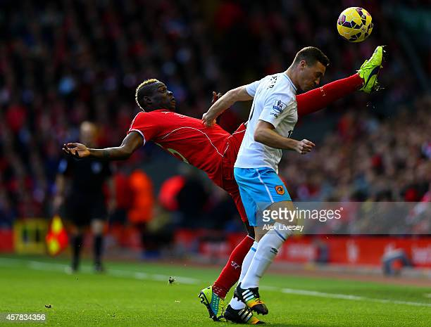 Mario Balotelli of Liverpool is challenged by James Chester of Hull City during the Barclays Premier League match between Liverpool and Hull City at...