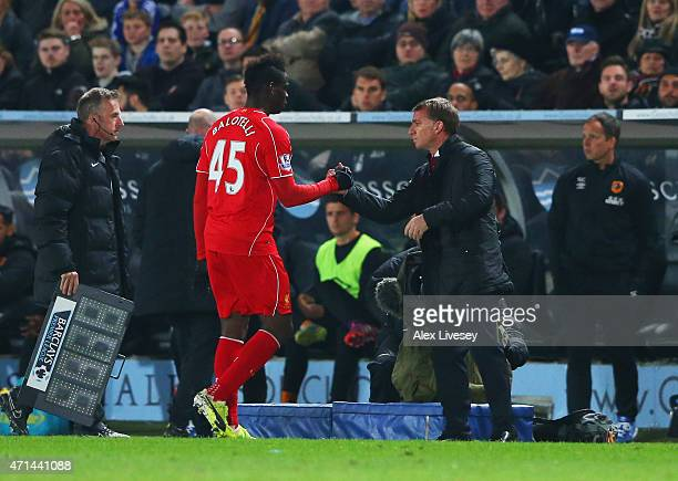 Mario Balotelli of Liverpool shakes hands with Brendan Rodgers manager of Liverpool as he is substituted during the Barclays Premier League match...