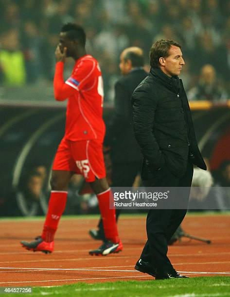 Mario Balotelli of Liverpool walks past Brendan Rodgers manager of Liverpool as he is substituted during the UEFA Europa League Round of 32 second...