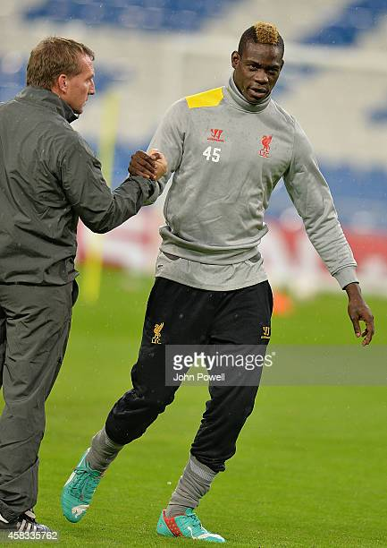 Mario Balotelli of Liverpool with Liverpool manager Brendan Rodgers during a training session ahead of the UEFA Champions League match against Real...