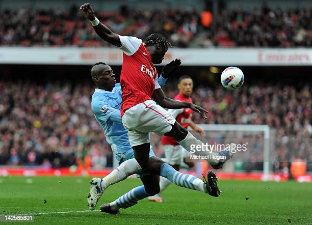 Mario Balotelli of Man City clashes with Bacary Sagna of Arsenal during the Barclays Premier League match between Arsenal and Manchester City at...