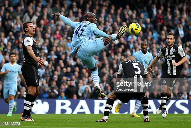 Mario Balotelli of Manchester City beats Danny Simpson of Newcastle United to the ball during the Barclays Premier League match between Manchester...