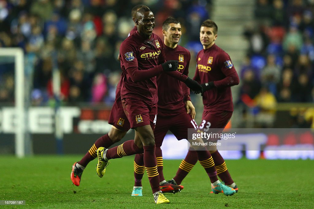 Mario Balotelli (L) of Manchester City celebrates after scoring his sides opening goal during the Barclays Premier League match between Wigan Athletic and Manchester City at the DW Stadium on November 28, 2012 in Wigan, England.