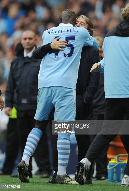 Mario Balotelli of Manchester City celebrates scoring to make it 10 with manager Roberto Mancini during the Barclays Premier League match between...