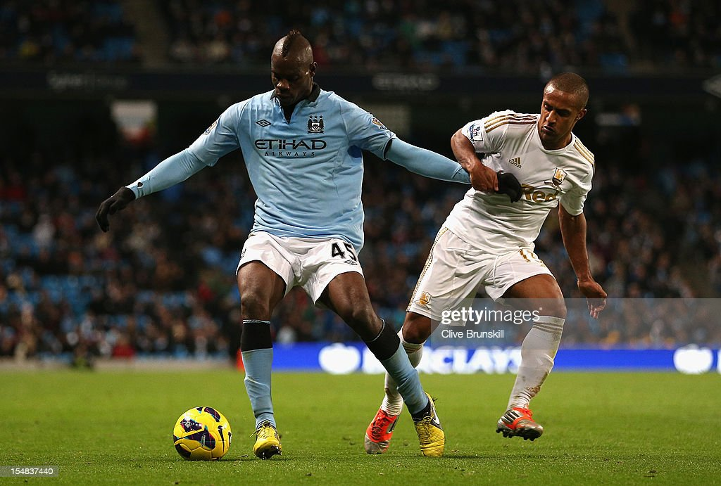 <a gi-track='captionPersonalityLinkClicked' href=/galleries/search?phrase=Mario+Balotelli&family=editorial&specificpeople=4940446 ng-click='$event.stopPropagation()'>Mario Balotelli</a> of Manchester City competes with <a gi-track='captionPersonalityLinkClicked' href=/galleries/search?phrase=Wayne+Routledge&family=editorial&specificpeople=206672 ng-click='$event.stopPropagation()'>Wayne Routledge</a> of Swansea City during the Barclays Premier League match between Manchester City and Swansea City at the Etihad Stadium on October 27, 2012 in Manchester, England.