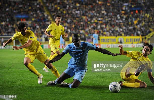 Mario Balotelli of Manchester City FC is fouled in the penalty aeria by Mateo Musacchio and Gonzalo Rodriguez of Villarreal CF during the UEFA...