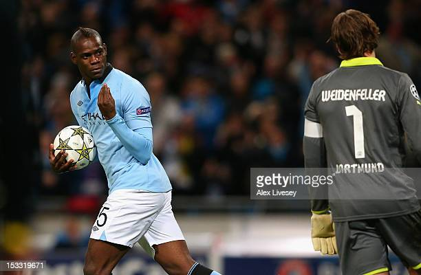 Mario Balotelli of Manchester City gestures to Roman Weidenfeller of Borussia Dortmund after scoring an equalising penalty kick during the UEFA...