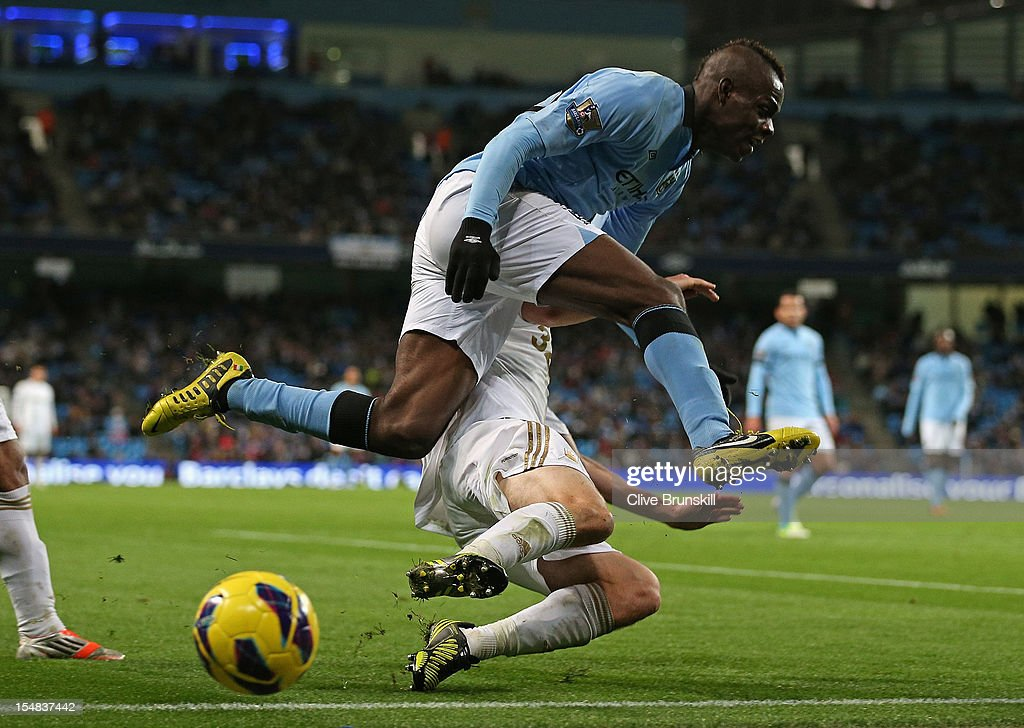 <a gi-track='captionPersonalityLinkClicked' href=/galleries/search?phrase=Mario+Balotelli&family=editorial&specificpeople=4940446 ng-click='$event.stopPropagation()'>Mario Balotelli</a> of Manchester City hurdles the tackle of <a gi-track='captionPersonalityLinkClicked' href=/galleries/search?phrase=Wayne+Routledge&family=editorial&specificpeople=206672 ng-click='$event.stopPropagation()'>Wayne Routledge</a> of Swansea City during the Barclays Premier League match between Manchester City and Swansea City at the Etihad Stadium on October 27, 2012 in Manchester, England.