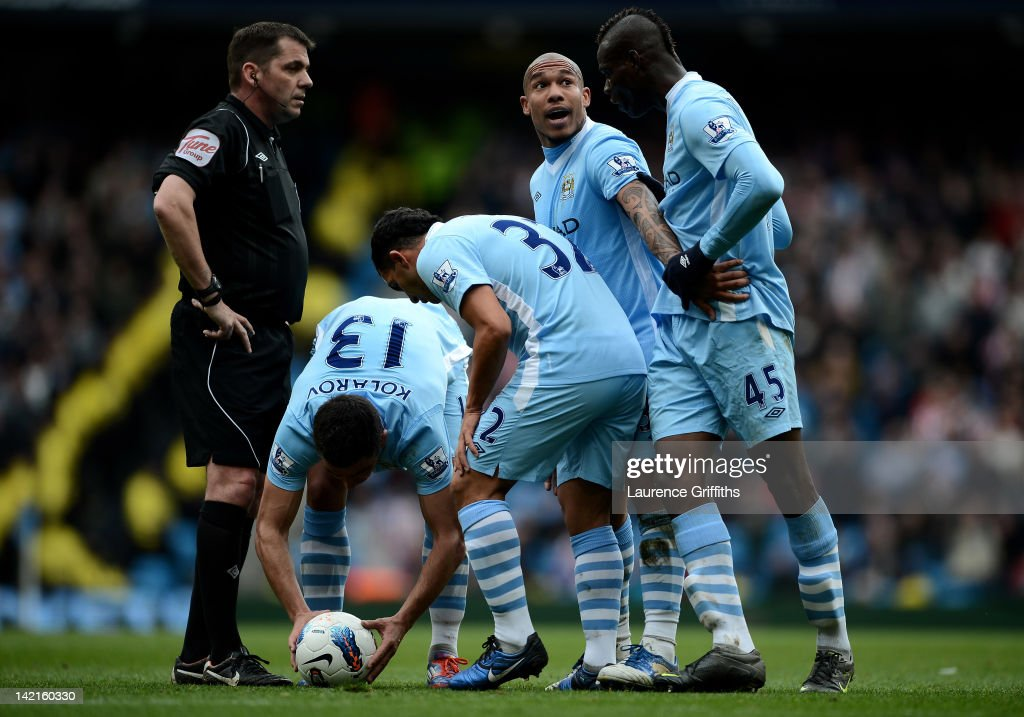 Mario Balotelli of Manchester City is restrained by team mate Nigel de Jong during the Barclays Premier League match between Manchester City and...