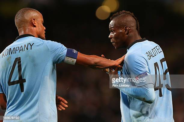 Mario Balotelli of Manchester City is restrained by teammate Vincent Kompany as he protests to Referee Peter Rasmussen after he denied him a penalty...