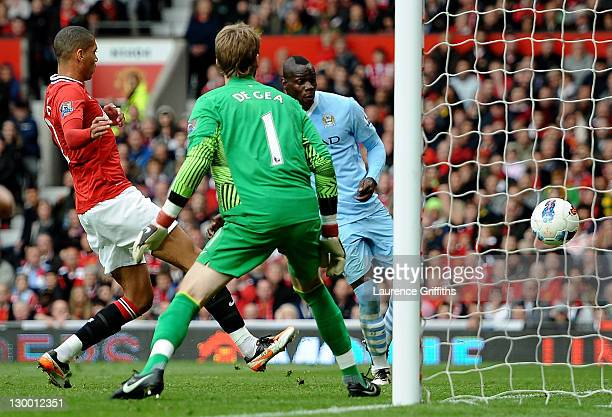 Mario Balotelli of Manchester City scores his team's second goal during the Barclays Premier League match between Manchester United and Manchester...