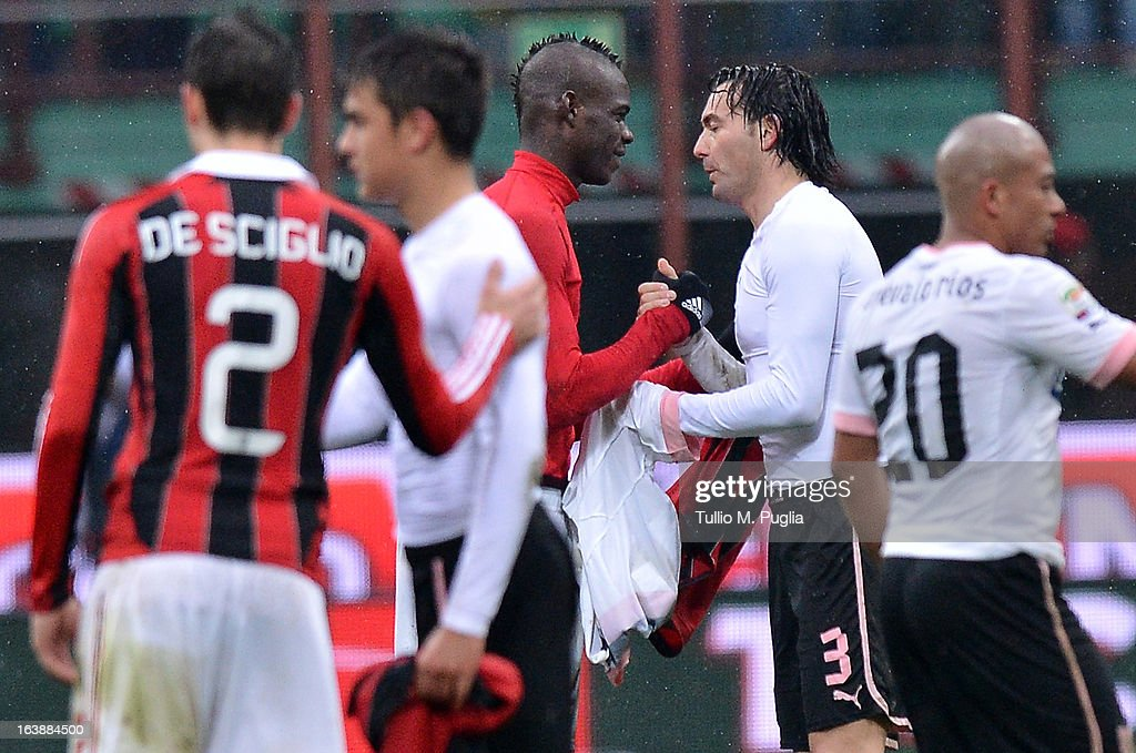 Mario Balotelli (C) of Milan and Salvatore Aronica (2nd-R) of Palermo chance their club shirts after the Serie A match between AC Milan and US Citta di Palermo at San Siro Stadium on March 17, 2013 in Milan, Italy.