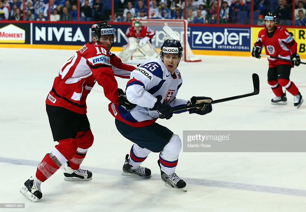 Mario Bliznak (R) of Slovakia and Daniel Oberkofler (L) of Austria battle for the puck during the IIHF World Championship group H match between Slovakia and Austria at Hartwall Areena on May 10, 2013 in Helsinki, Finland.