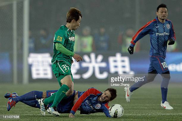 Mario Bozic of Shanghai Shenhua clashes with opponent Piao Cheng of Beijing Guoan during the Chinese Super League match at Workers Stadium on March...