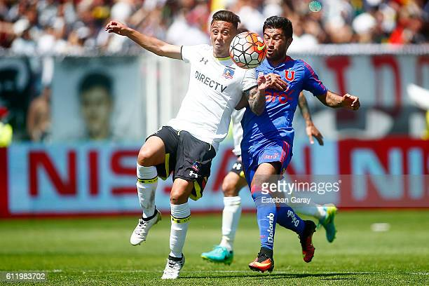 Mario Brice–o of Universidad de Chile fights for the ball with Martin Rodriguez of Colo Colo during a match between Colo Colo and Universidad de...