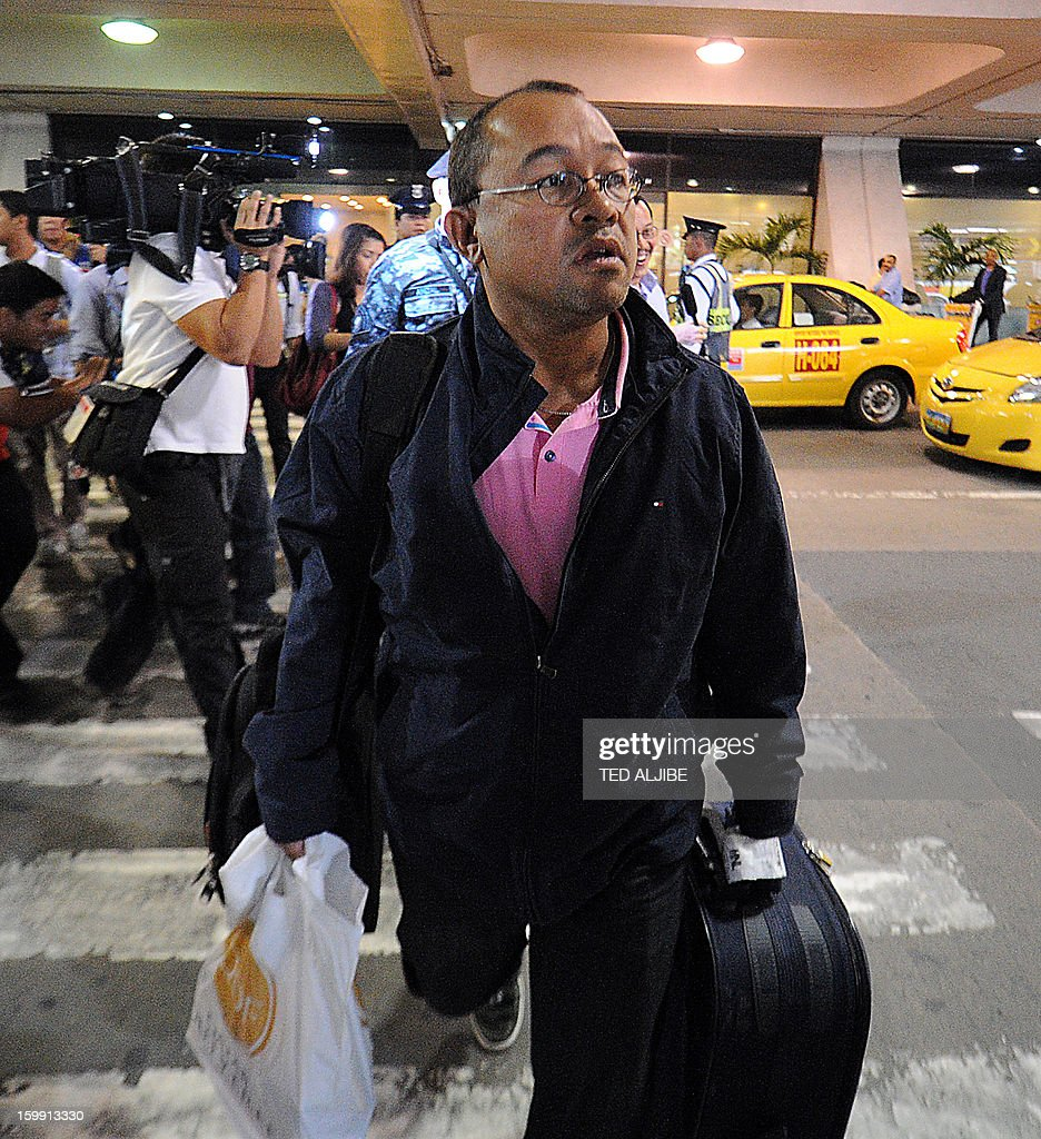 Mario Catiis (C), a Filipino labourer working at the time when Islamists siezed workers at a gas plant in Algeria, but was not taken hostage, is mobbed by members of the media shortly after arriving at the international airport in Manila on January 23, 2013. Islamic militants used foreign hostages as human shields to stop Algerian troops aboard helicopters from strafing them with gunfire, Filipino survivor Joseph Balmaceda of the four-day bloodbath recounted January 21. AFP PHOTO/TED ALJIBE