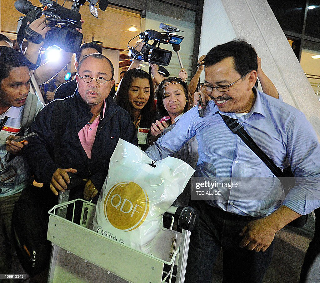 Mario Catiis (L) and Ramon Tertosa (R), Filipino labourers working at the time when Islamists siezed workers at a gas plant in Algeria, but were not taken hostage, are mobbed by members of the media shortly after arriving at the international airport in Manila on January 23, 2013. Islamic militants used foreign hostages as human shields to stop Algerian troops aboard helicopters from strafing them with gunfire, Filipino survivor Joseph Balmaceda of the four-day bloodbath recounted January 21. AFP PHOTO/TED ALJIBE