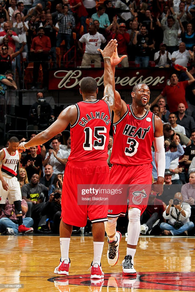 Mario Chalmers #15 of the Miami Heat celebrates with teammate Dwyane Wade #3 after making a three-pointer against the Portland Trail Blazers on February 12, 2013 at American Airlines Arena in Miami, Florida.