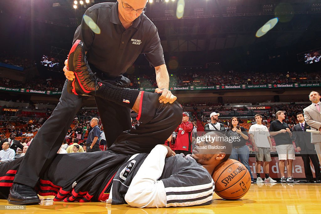 Mario Chalmers #15 of the Miami Heat stretches with a trainer before a game against the Indiana Pacers on March 10, 2013 at American Airlines Arena in Miami, Florida.