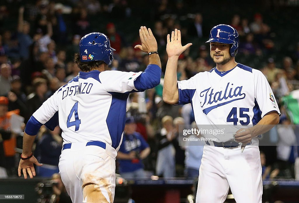 Mario Chiarini #45 of Italy high fives Mike Costanzo #4 after both scored runs against Canada during the seventh inning of the World Baseball Classic First Round Group D game at Chase Field on March 8, 2013 in Phoenix, Arizona.
