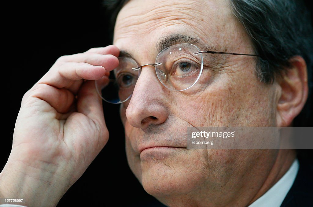 Mario Draghi, president of the European Central Bank (ECB), adjusts his spectacles during a news conference at the bank's headquarters in Frankfurt, Germany, on Thursday, Dec. 6, 2012. The European Central Bank cut its economic and inflation forecasts and Draghi said weakness will persist into next year, leaving the door ajar for further interest-rate cuts. Photographer: Ralph Orlowski/Bloomberg via Getty Images
