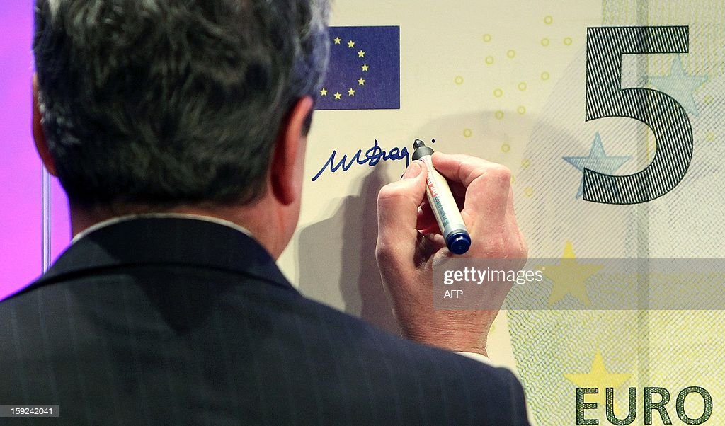 Mario Draghi, President of the European Central Bank, (ECB) is signing a giant five euro note (€5) during the unveiling ceremony of the new 5 euros s Banknote in Frankfurt/Main, Germany, on January 10, 2013. AFP PHOTO / DANIEL ROLAND