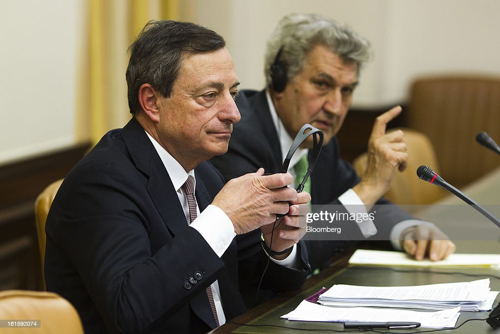 Mario Draghi, president of the European Central Bank (ECB), left, adjusts his headphones while Jesus Posada, president of the Congress of Deputies, speaks during a news conference at the Spanish Congress in Madrid, Spain, on Tuesday, Feb. 12, 2013. Draghi said politicians should refrain from calling for intervention on the euro's exchange rate. Photographer: Angel Navarrete/Bloomberg via Getty Images