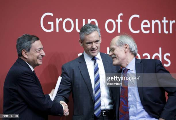 Mario Draghi president of the European Central Bank left shakes hands with William Coen secretary general of the Basel Committee center as Stefan...