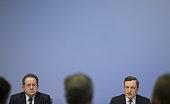Mario Draghi president of the European Central Bank right speaks as Vitor Constancio vice president of the European Central Bank looks on during a...