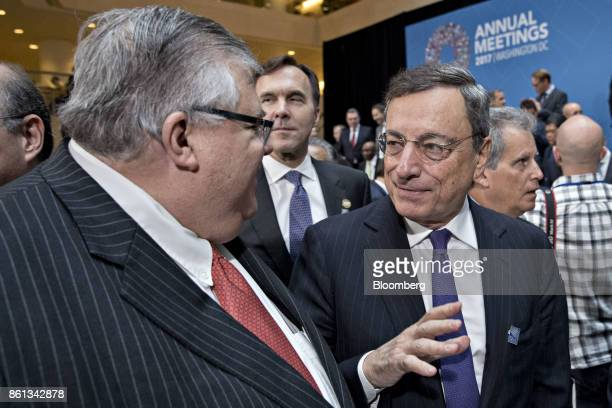 Mario Draghi president of the European Central Bank right speaks with Agustin Carstens governor of the Bank of Mexico during the International...