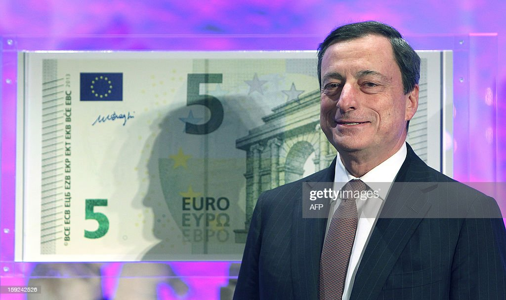 Mario Draghi, President of the European Central Bank, (ECB) smiles in front of a giant five euro note (€5) during the unveiling ceremony of the new 5 euros sbanknote in Frankfurt/Main, on January 10, 2013.