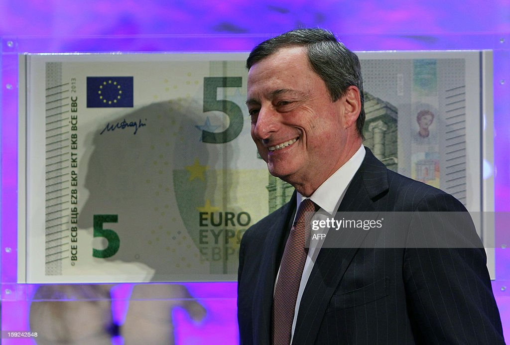 Mario Draghi, President of the European Central Bank, (ECB) smiles in front of a giant five euro note (€5) during the unveiling ceremony of the new 5 Euros banknote in Frankfurt/Main, on January 10, 2013.